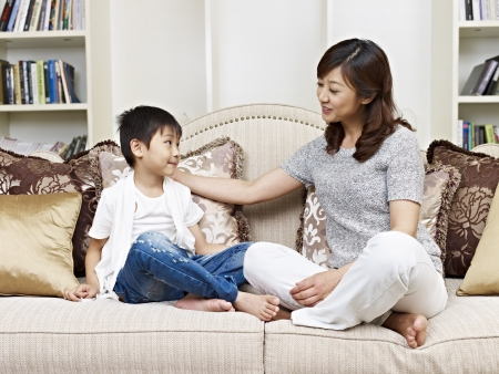 21144465 - asian mother and son having a conversation on couch at home