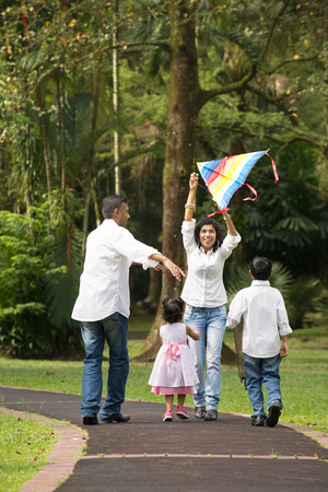 26880286 - indian family playing kite in the outdoor park