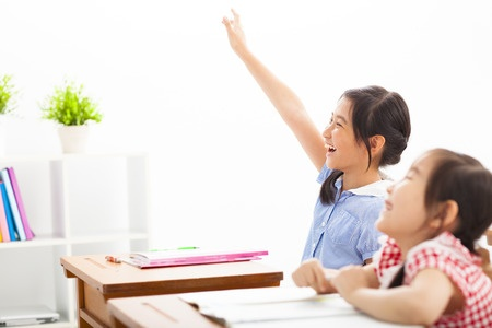 38126706 - happy school children  raised hands in class