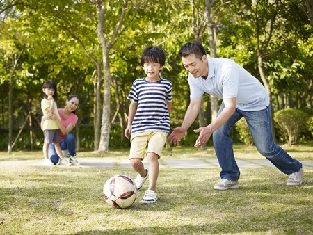 41791534 - asian father teaching son to play soccer (football) in a park