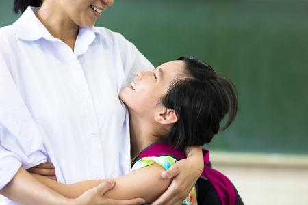 43490556 - happy  girl hugging her mother in classroom