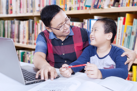 45124973 - photo of young asian man talking with a little boy while teaching him in the library