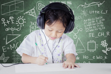 45508612 - female kindergarten school student studying in the classroom while wearing headphones and write on the paper