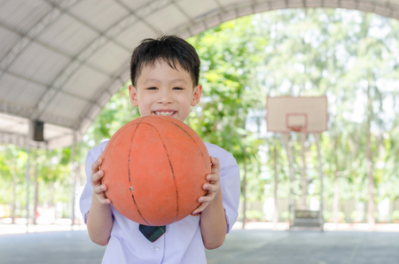 48010312 - little asian student holding basketball at school