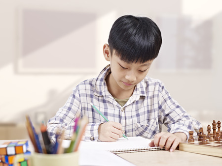 49254439 - 10 year-old asian elementary schoolboy doing homework at home.