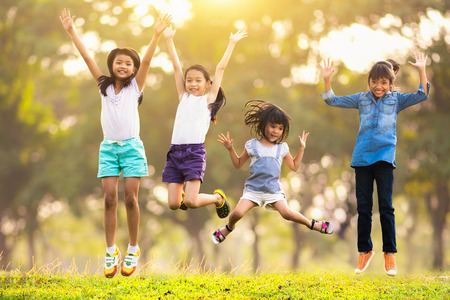 52257442 - joyful happy asian family jumping together at outdoor park