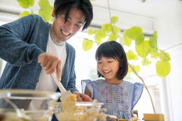 Father and daughter smiling and having fun whilst baking together in the kitchen. Kyoto, Japan. May 2016
