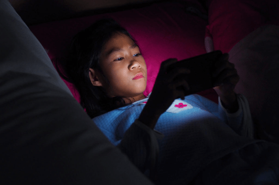 kid on mobile phone at night
