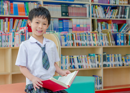 35107330 - asian schoolboy reading book in school library