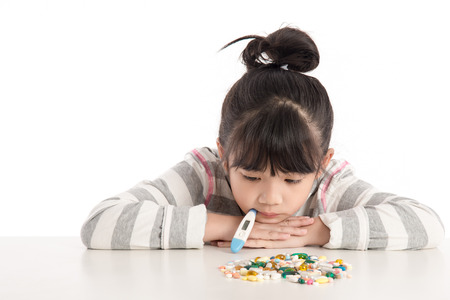 41724633 - sick girl looking pills on white table,isolated