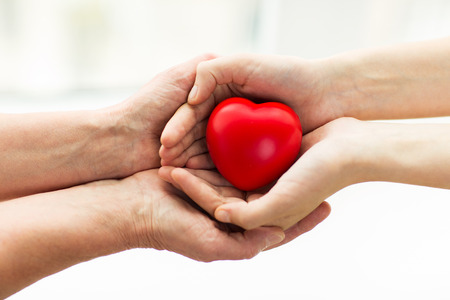 47872526 - people, age, family, love and health care concept - close up of senior woman and young woman hands holding red heart