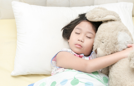 72335209 - cute little asian girl sleep and hug teddy bear on bed in the bedroom